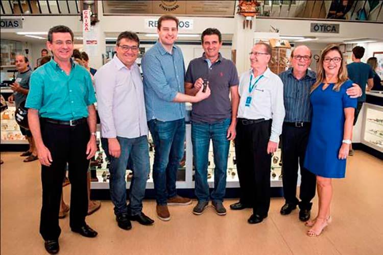 ogério Ivan Santos (ao centro) recebeu a chave do Volkswagen UP! do vice-presidente da CDL Blumenau, Ewald Fischer Neto na Relojoaria e Ótica Universal.