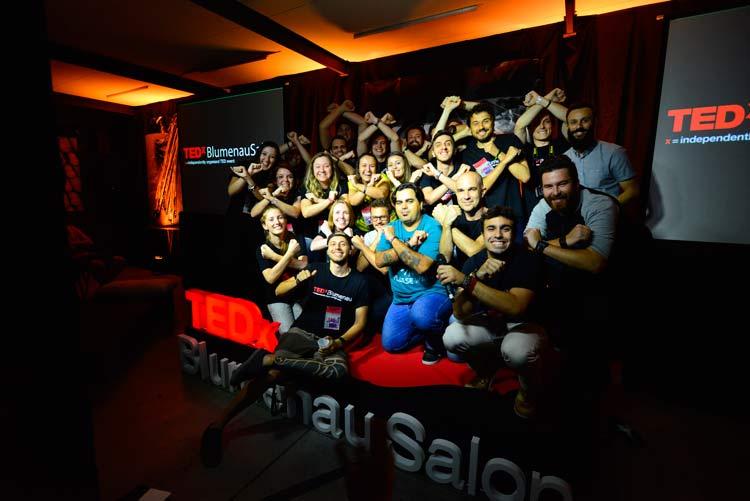 Equipe de voluntários no palco com os speakers de música do TEDxBlumenauSalon | Imagem: Blink Studios